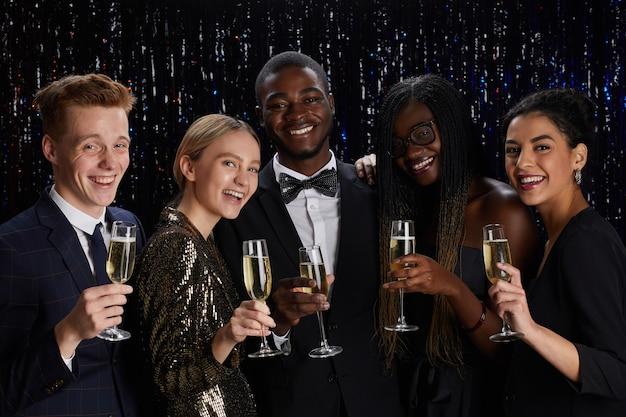 Retrato de um grupo multiétnico de amigos segurando taças de champanhe e sorrindo para a câmera enquanto desfruta de uma festa elegante.