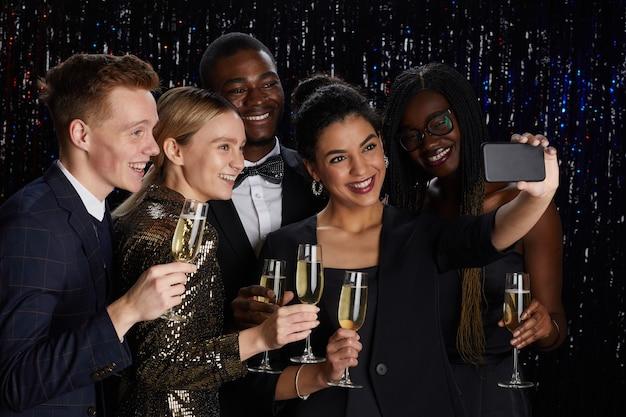 Retrato de um grupo multiétnico de amigos segurando taças de champanhe e tirando uma selfie juntos enquanto desfrutam de uma festa elegante.