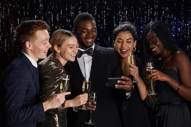 Retrato de um grupo multiétnico de amigos segurando taças de champanhe e transmitindo ao vivo online enquanto desfruta de uma festa elegante.
