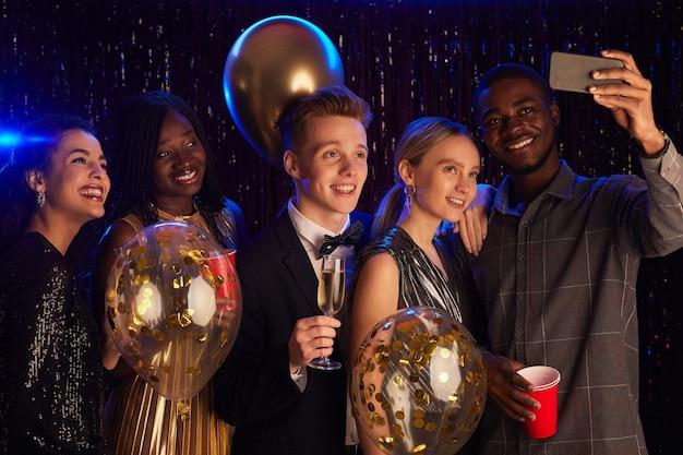 Retrato de um grupo multiétnico de amigos tirando uma selfie com balões enquanto desfruta da festa de aniversário ou da noite do baile