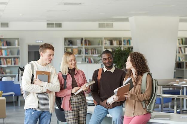 Retrato de um grupo multiétnico de estudantes em pé na biblioteca da faculdade, conversando, segurando livros e mochilas, acima