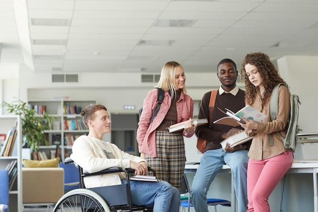 Retrato de um grupo multiétnico de estudantes na biblioteca da faculdade com um menino em uma cadeira de rodas em primeiro plano
