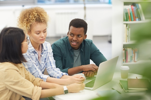 Retrato de um grupo multiétnico de estudantes usando um laptop