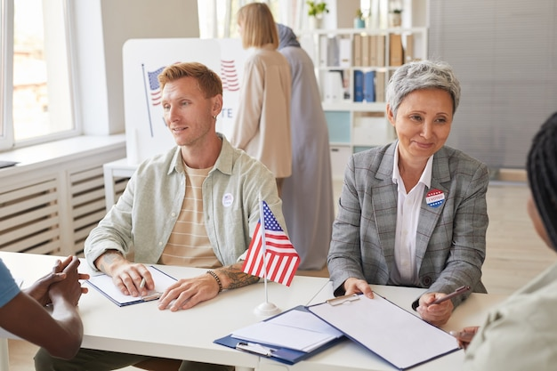 Retrato de um grupo multiétnico de pessoas votando em uma mesa de votação decorada com bandeiras americanas, copie o espaço