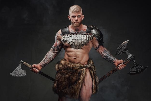 Retrato de um guerreiro forte e tatuado em armadura leve e pele com dois machados no escuro