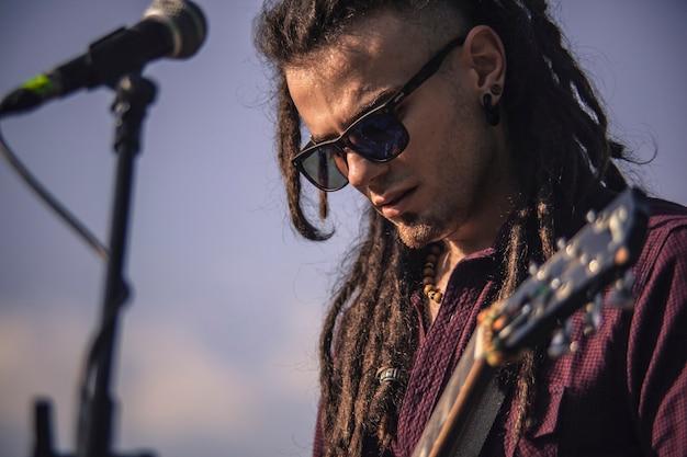 Retrato de um guitarrista ao pôr do sol durante um show ao vivo