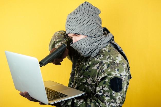 Retrato de um hacker man terroris em uma camuflagem e uma máscara está olhando para o laptop.
