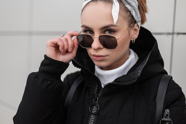 Retrato de um hipster de mulher jovem e bonita elegante com belos olhos com um penteado elegante em elegantes óculos de sol em um golfe de malha com uma jaqueta de inverno perto de uma parede branca. garota incrível.