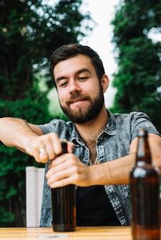 Retrato, de, um, homem, abertura, a, garrafa cerveja, boné