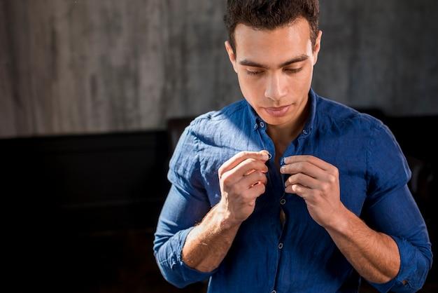 Retrato, de, um, homem, abotoando, seu, camisa azul