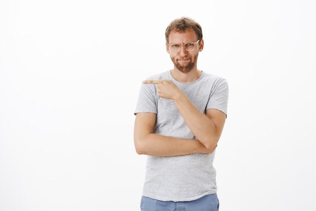 Retrato de um homem adulto bonito, intenso e irritado, com cerdas nos óculos, franzindo a testa e franzindo os lábios, fazendo o homem apontar para um colega de trabalho que ele odeia por causa de uma parede branca