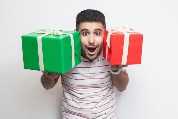 Retrato de um homem adulto jovem atraente chocado incrível em pé de t-shirt, segurando duas caixas de presente grande perto do rosto, olhando para a câmera. foto de estúdio, fundo branco, isolado, interno