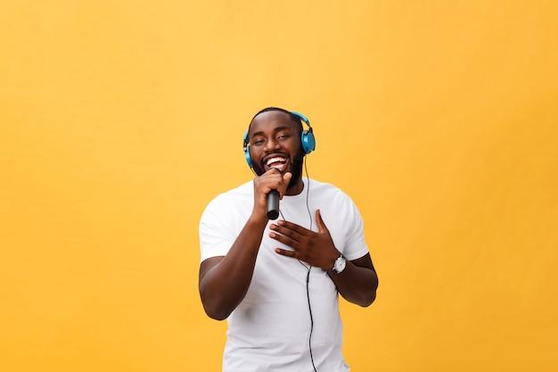 Retrato de um homem africano alegre segurando um microfone e fones de ouvido na cabeça, ouvindo música cantando música