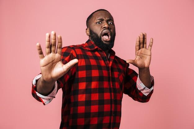 Retrato de um homem africano assustado, vestindo uma camisa xadrez, isolado na parede rosa, fazendo uma careta