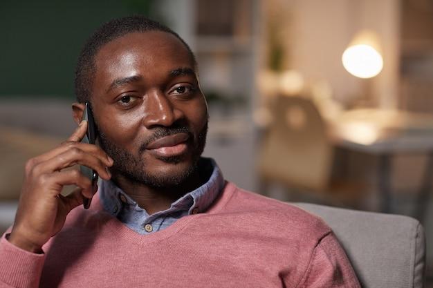 Retrato de um homem africano bonito olhando para a câmera enquanto conversa no celular