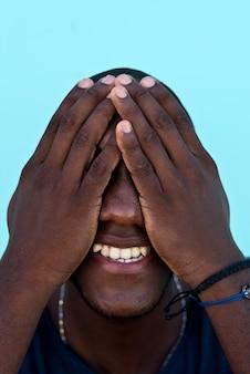 Retrato de um homem africano, cobrindo o rosto com as mãos
