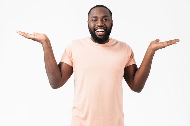 Retrato de um homem africano confuso, vestindo uma camiseta em pé, isolado na parede branca, apresentando espaço de cópia