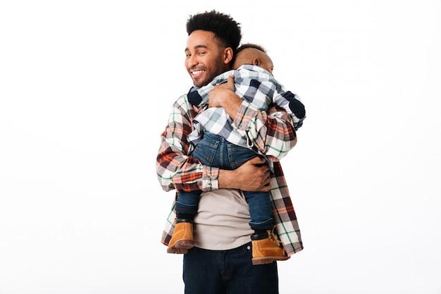 Retrato de um homem africano feliz, abraçando seu filho pequeno