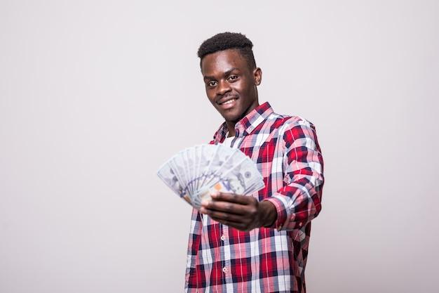 Retrato de um homem africano feliz e animado segurando um monte de notas de dinheiro e parecendo isolado