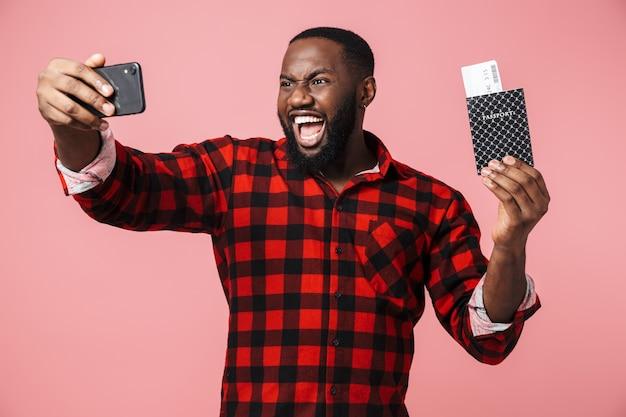Retrato de um homem africano feliz, vestindo uma camisa em pé, isolado na parede rosa, tirando uma selfie, mostrando o passaporte com as passagens aéreas