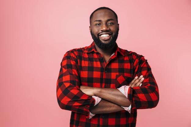 Retrato de um homem africano feliz, vestindo uma camisa xadrez em pé, isolado na parede rosa, com os braços cruzados