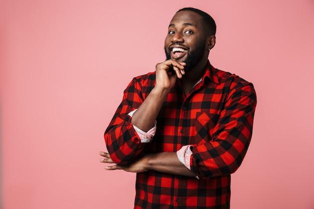 Retrato de um homem africano feliz, vestindo uma camisa xadrez em pé, isolado na parede rosa, olhando para a câmera