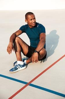 Retrato de um homem africano fitness sorridente em fones de ouvido descansando