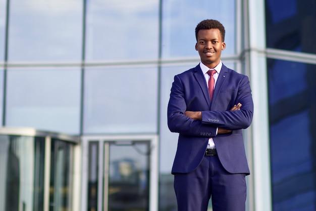 Retrato de um homem africano negro sério confiante e bem sucedido, um jovem empresário afro-americano de terno formal com gravata, escritório comercial ao ar livre com as mãos cruzadas