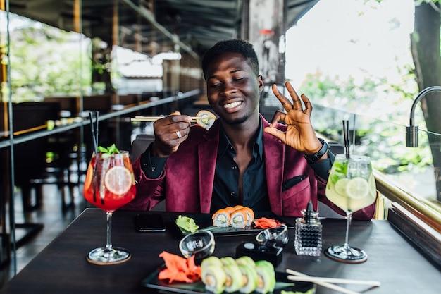 Retrato de um homem africano segurando pauzinhos rolos de sushi. ok, sinal.
