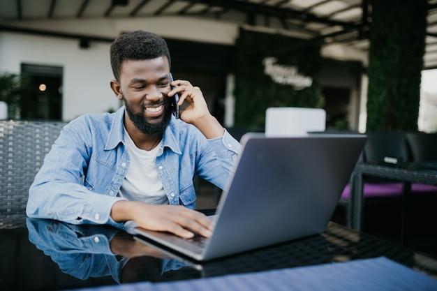Retrato de um homem africano sorridente, falando no celular enquanto está sentado em um café com um laptop