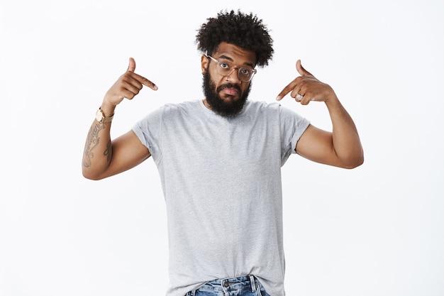Retrato de um homem afro-americano adulto com barba e cabelos cacheados em óculos apontando para si mesmo com uma expressão nada ruim, levantando o queixo e levantando as sobrancelhas, questionado e inseguro, ouvindo a opinião