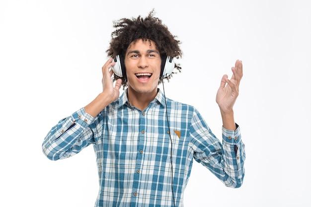 Retrato de um homem afro-americano alegre com cabelo encaracolado ouvindo música em fones de ouvido isolados em uma parede branca.