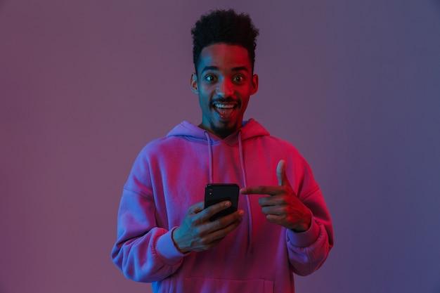 Retrato de um homem afro-americano animado com um capuz colorido, segurando e apontando o dedo para o celular isolado sobre a parede violeta