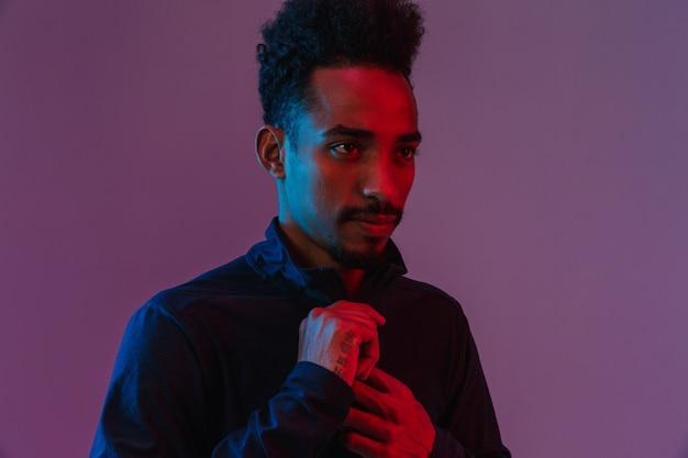 Retrato de um homem afro-americano barbudo em roupas esportivas posando isolado na parede violeta
