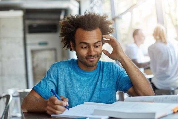 Retrato de um homem afro-americano bonito com cabelo espesso, sentado à mesa na cantina da universidade, escrevendo notas, coçando a cabeça, sem saber algo, preparando uma pesquisa científica ou projeto