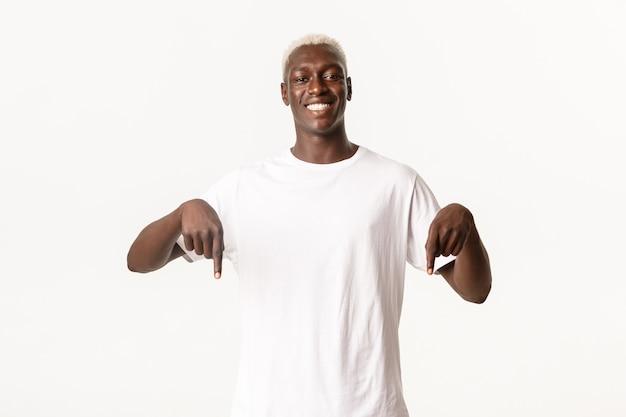 Retrato de um homem afro-americano bonito e elegante, sorrindo satisfeito e apontando o dedo para baixo