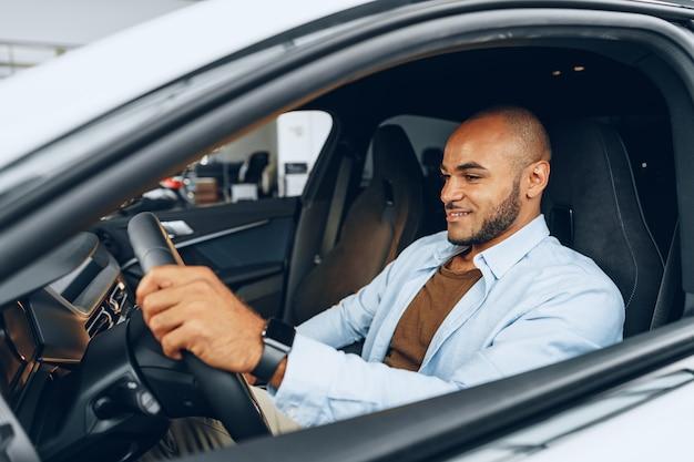 Retrato de um homem afro-americano bonito e feliz sentado em seu carro recém-comprado de perto