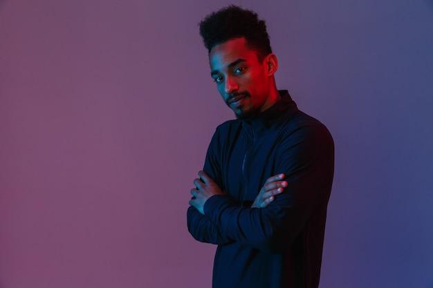 Retrato de um homem afro-americano bonito em roupas esportivas posando com os braços cruzados isolados sobre a parede violeta
