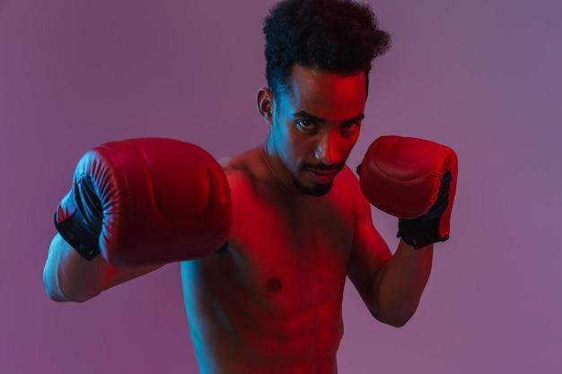 Retrato de um homem afro-americano bonito seminu posando com luvas de boxe isoladas sobre a parede violeta
