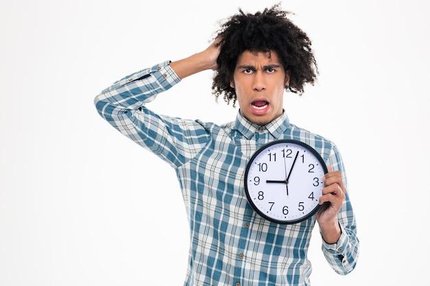 Retrato de um homem afro-americano chocado segurando um relógio de parede isolado em uma parede branca