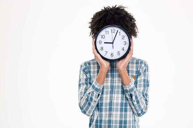 Retrato de um homem afro-americano cobrindo o rosto com um relógio de parede isolado em uma parede branca