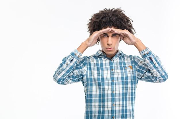 Retrato de um homem afro-americano com cabelo encaracolado, olhando para a distância, isolado em uma parede branca