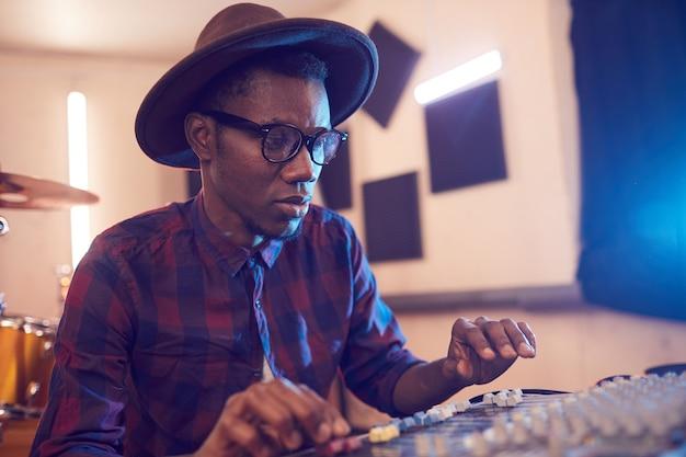 Retrato de um homem afro-americano contemporâneo escrevendo música em um estúdio de gravação