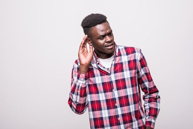 Retrato de um homem afro-americano curioso tentando ouvir algo, mantendo a mão no ouvido isolado