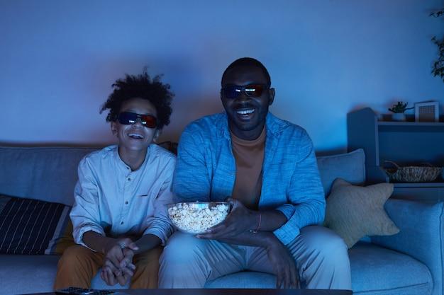 Retrato de um homem afro-americano e seu filho adolescente sentados juntos no sofá na sala de estar rindo enquanto assistem um filme em 3d e comem pipoca