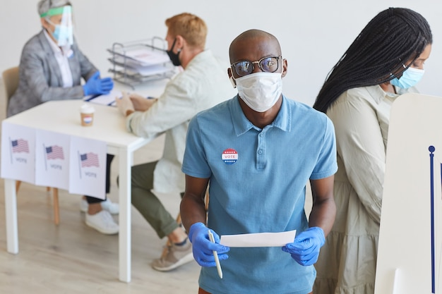 Retrato de um homem afro-americano em frente à cabine de votação decorada com a bandeira dos eua e no dia da eleição pós-pandemia, copie o espaço