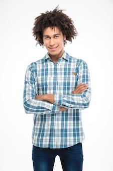 Retrato de um homem afro-americano feliz em pé com os braços cruzados e parecendo isolado em uma parede branca
