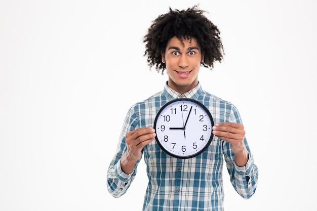 Retrato de um homem afro-americano feliz segurando um relógio de parede isolado em uma parede branca