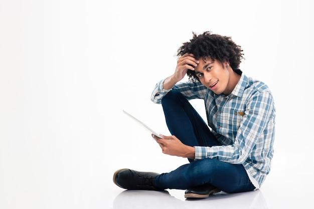 Retrato de um homem afro-americano feliz sentado no chão com um laptop isolado em uma parede branca.