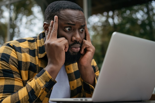 Retrato de um homem afro-americano pensativo usando um laptop e olhando para a tela digital